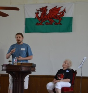 Nic Schumer regales the congregation with a history in the crucial role that churches played in preserving Welsh culture, as Carol Ellis, Gamanfa Ganu leader, looks on.
